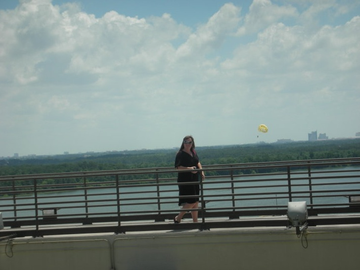 Me on the catwalk with a parasailer on Bay Lake in the background