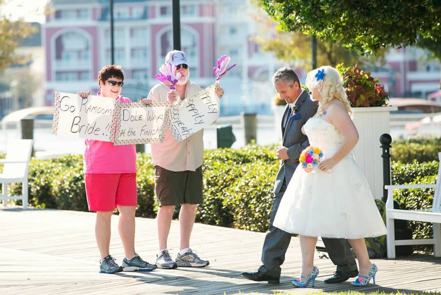 Spectators Hold Up Race Signs for runDisney Bride on Wedding Day at Walt Disney World
